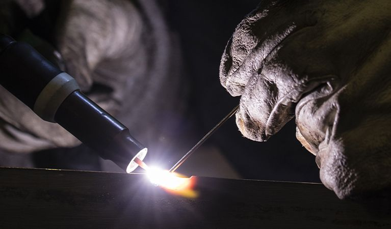 Two gloved hands welding with a bright white light on the surface.jpg