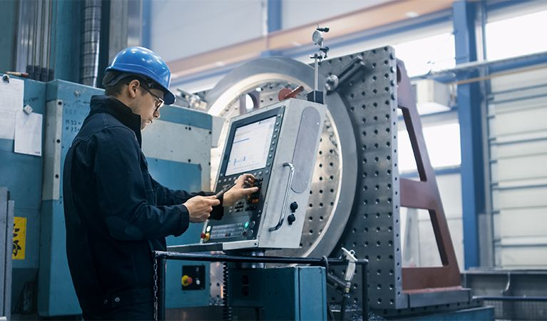 Male CNC Operator in a blue hard hat standing in front of a CNC machine.jpg